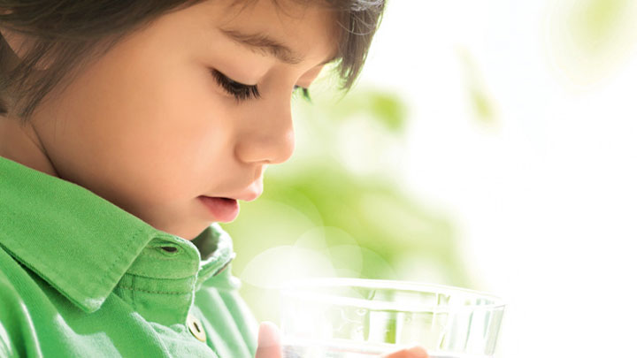 A boy looking into a glass of clean water