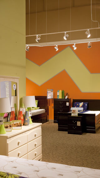Ashley Furniture HomeStore lights a n accent wall with Track heads using LED Lamps