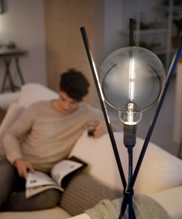Man reading next to a Philips Modern designed LED bulb