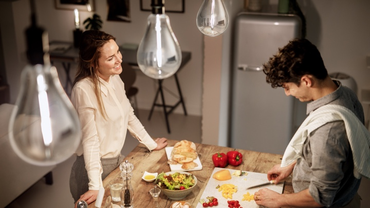 Top view of man and woman preparing dinner in well-lit kitchen