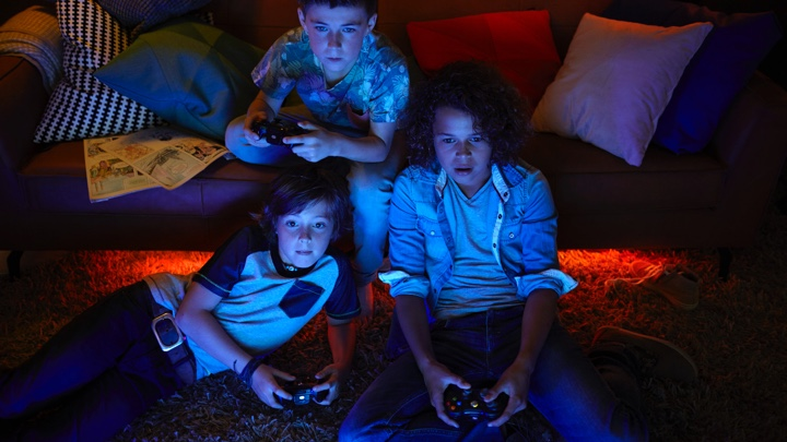 3 boys playing video games with ambiance lighting