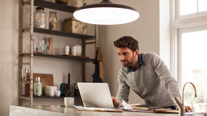 a man working at home under a smart luminaire
